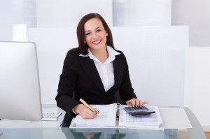 27864859 - portrait of happy businesswoman calculating tax at desk in office